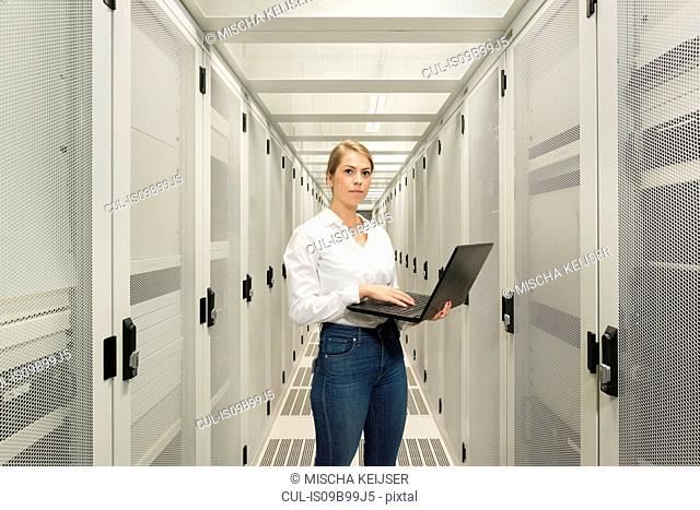 Portrait of young woman in data centre, using laptop