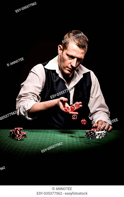 A male gambler rolls the dice after the betting