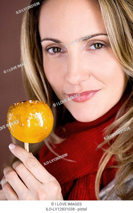 A mid adult woman holding a toffee apple