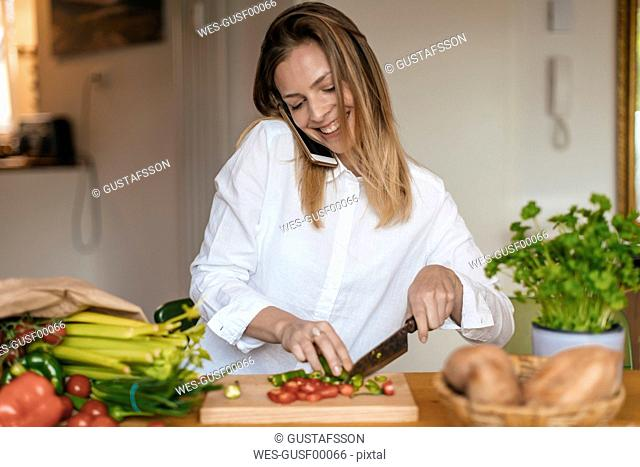 Smiling woman on the phone chopping vegetables in the kitchen