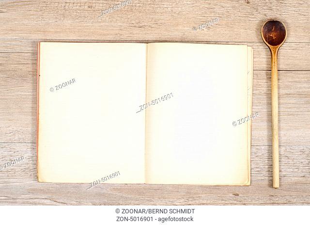 Altes Papier in einem Buch mit Kochlöffel auf einem Holztisch