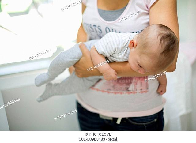 Mother carrying baby son upside down