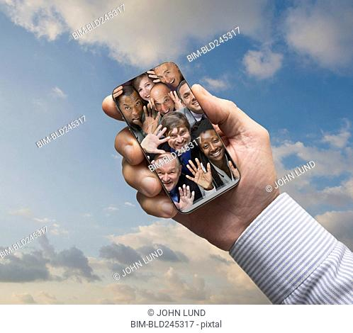 Hand of businessman holding social media cell phone in sky
