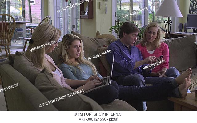 MS, DS, family of four sitting on a couch in their living room