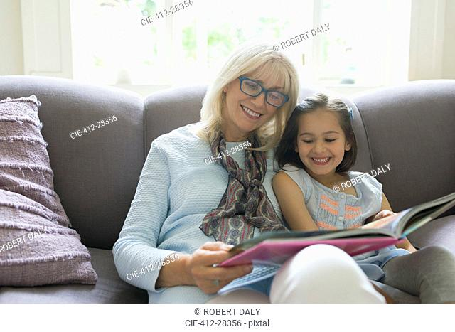 Grandmother and granddaughter reading book on living room sofa