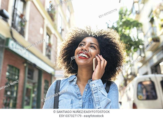 Beautiful afro american woman using her mobile in the street. Communication concept