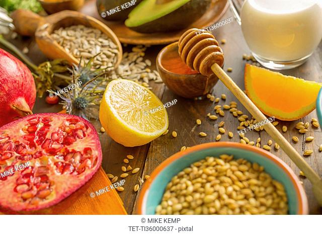 Wheat seeds, honey with dipper and fresh fruits