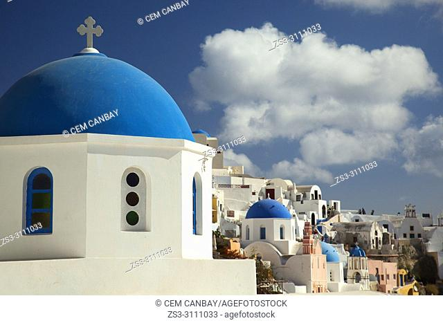 Blue domed churches in Oia village with the tourists taking photos at the background, Santorini, Cyclades Islands, Greek Islands, Greece, Europe