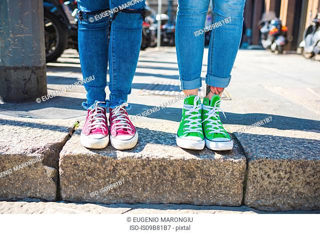 Women's feet in trainers on step, Milan, Italy