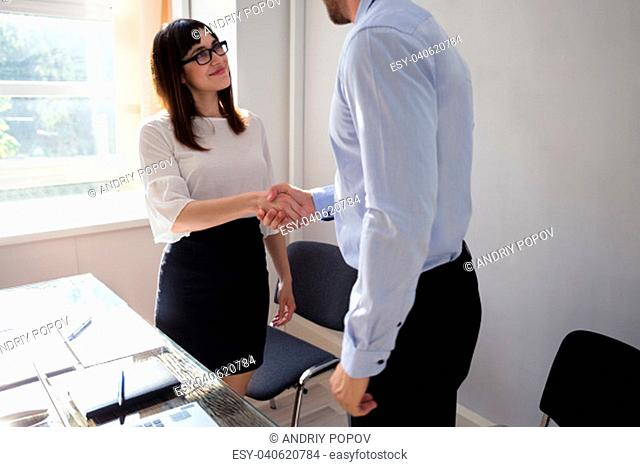 Smiling Young Businesswoman Shaking Hand With Her Partner At Workplace