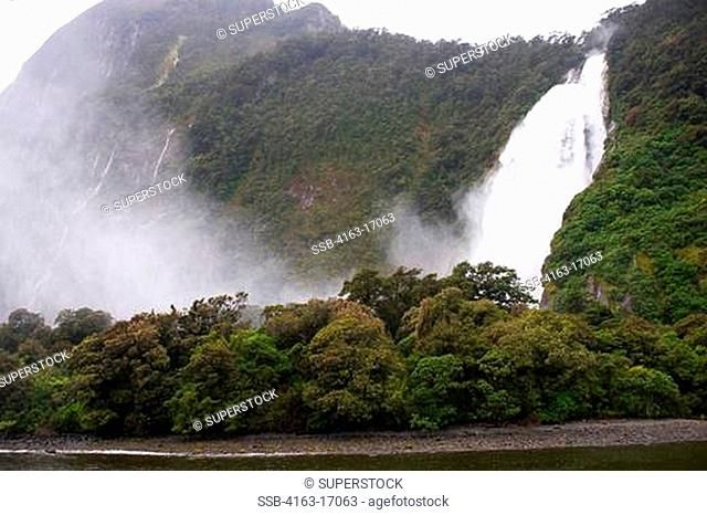 NEW ZEALAND, OCEANIA, SOUTH ISLAND, FIORDLAND NATIONAL PARK, MILFORD SOUND IN RAIN, WATERFALL