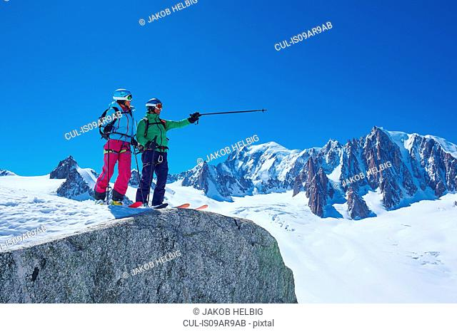 Male and female skiers pointing from ridge on Mont Blanc massif, Graian Alps, France