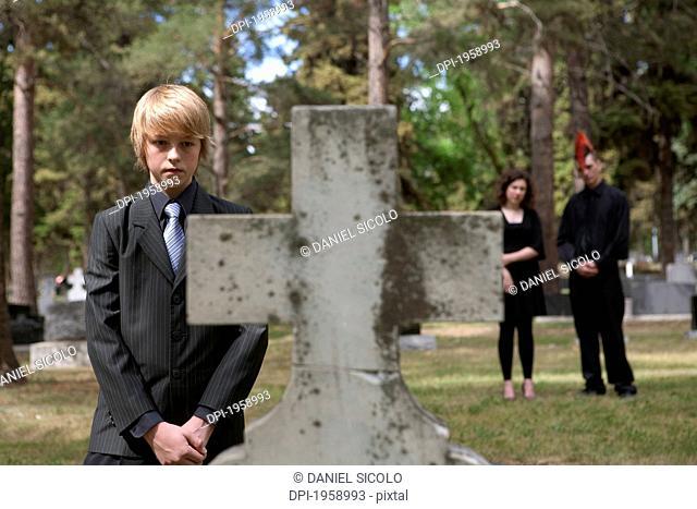 A Teenage Boy Visiting A Tombstone In A Cemetery; Edmonton, Alberta, Canada