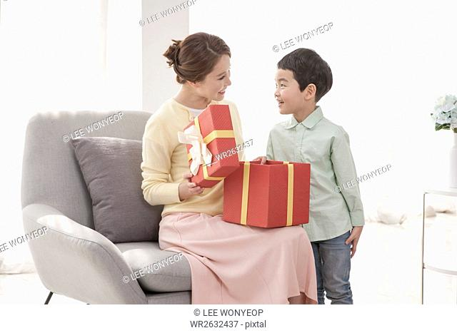 Loving mother and son opening present box smiling at each other