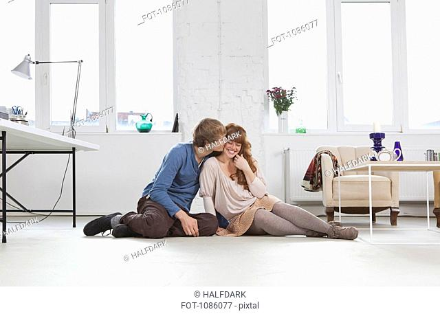 A young man kissing his girlfriend, side by side, sitting on floor