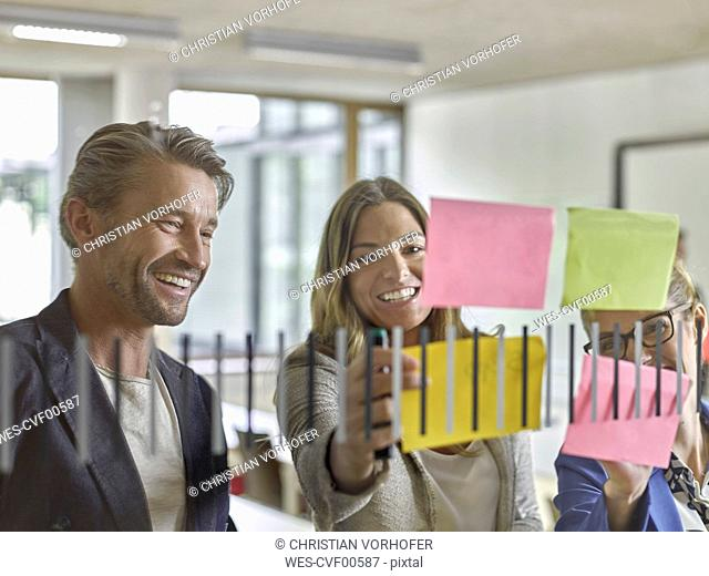 Happy colleagues discussing with sticky notes at glass pane