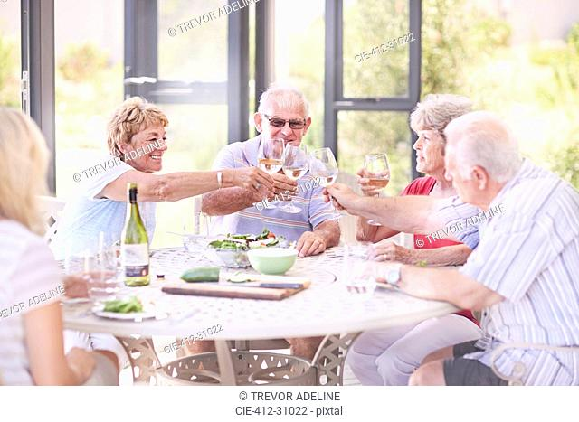 Senior adults toasting wine glasses at patio lunch