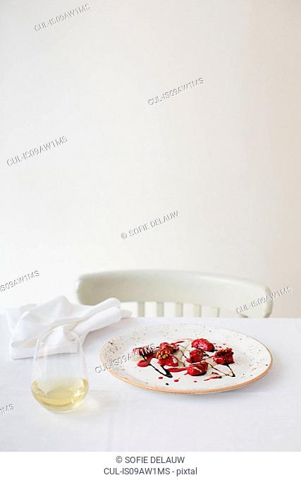 Table with plate of red beet ravioli with blue cheese and coffee sauce