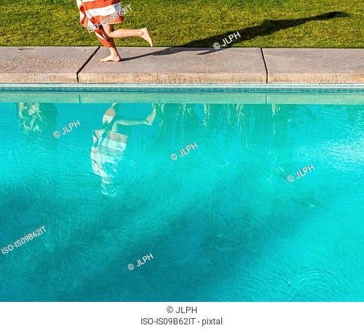 Waist down view of boy wrapped in towel running on poolside