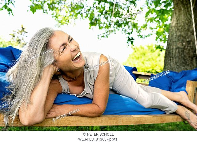 Laughing woman with long grey hair lying on a bed in garden