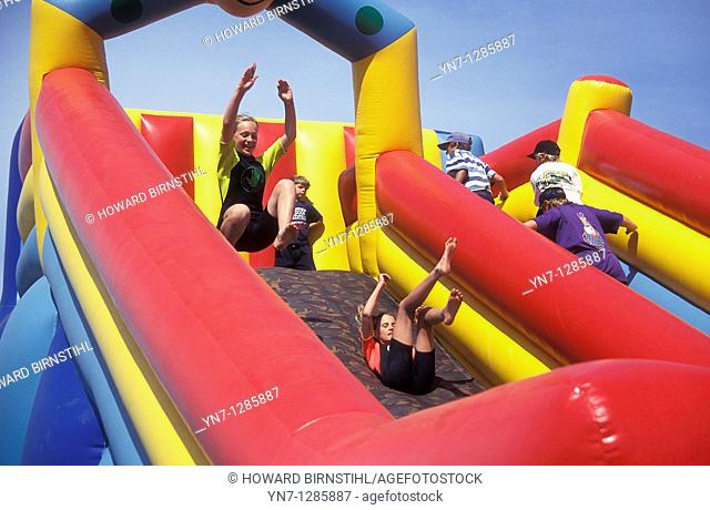 Kids having fun on big rubber slide