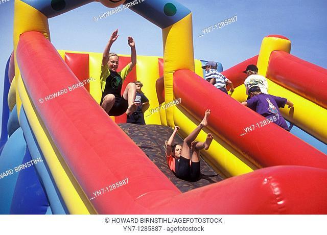 Kids having fun on big rubber slide