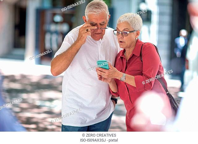 Senior man and woman reading smartphone in city