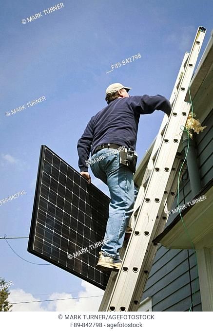 Man carries solar panel up ladder to roof
