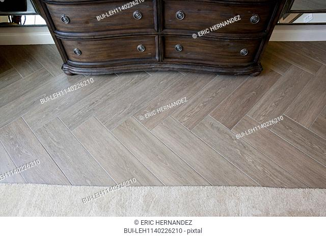 Close-up of wooden floor with cropped area rug and cabinet at home