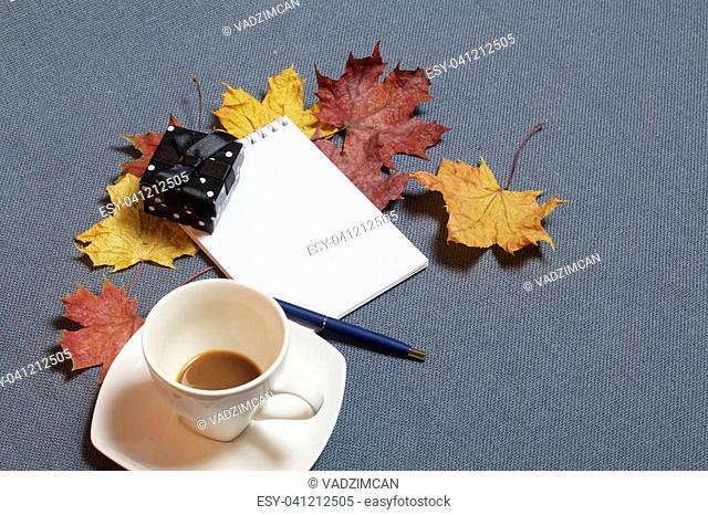 A cup with unapproved coffee. There is an open notepad and a pen. A black box with a gift. Fallen autumn leaves of yellow and red are scattered on the surface