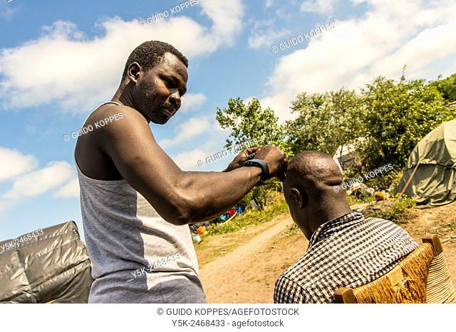 The Jungle, Calais, France. A Darfur, Sudan born illegal immigrant or migrant, shaving the head of a fellow refugee, while standing in front of an improvised...