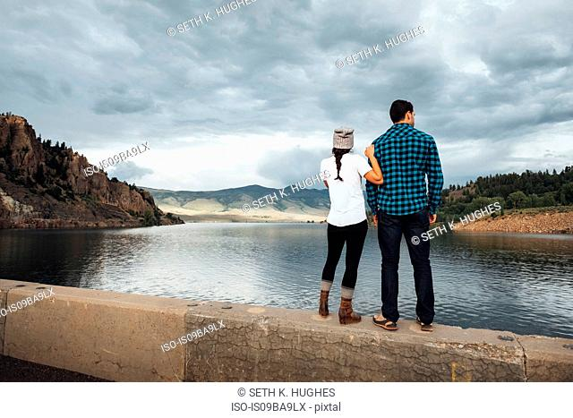 Couple standing on wall beside Dillon Reservoir, looking at view, rear view, Silverthorne, Colorado, USA