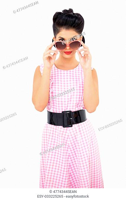 Stylish black hair model looking over her sunglasses on white background