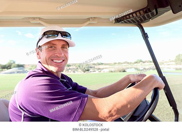 Portrait of smiling Hispanic man driving golf cart