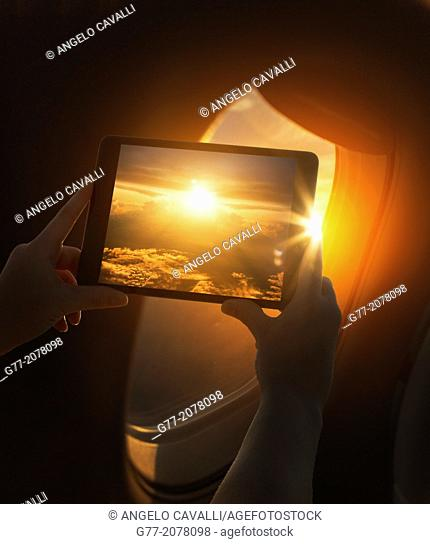 Woman on a plane taking picture of sunset with tablet