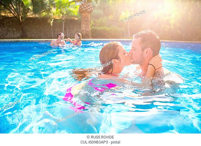 Couple in swimming pool kissing