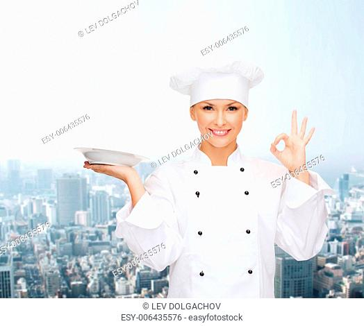 people, cooking and food concept - smiling female chef, cook or baker with empty plate showing ok sign over city background