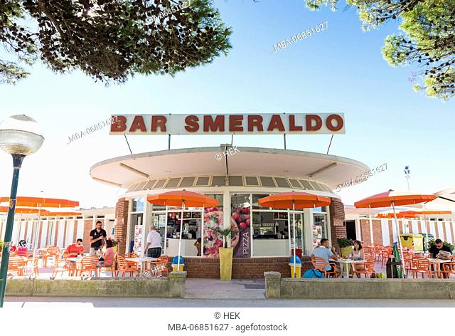 View of 'Smeralda' beach bar and guests sitting in front of it, architecture on the beach of Lignano