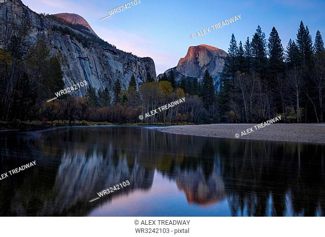 Half Dome mountain catches the last glow of sunset reflected in the Merced River in Yosemite National Park, UNESCO World Heritage Site, California