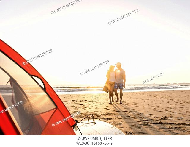 Romantic couple camping on the beach, doing a beach stroll at sunset