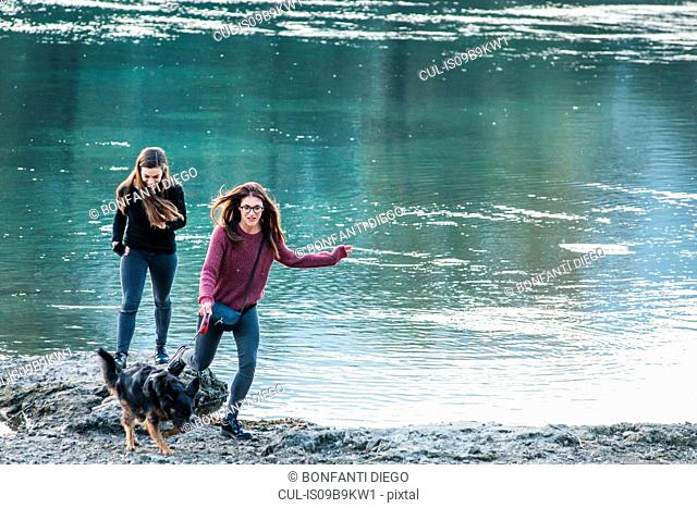 Two young women running with dog by river, Calolziocorte, Lombardy, Italy