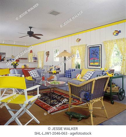 FAMILY ROOM - In pool house, white paneled walls, yellow trim, yellow tie back curtains, blue chambrey sofas with multi colored pillows, pattern and sold