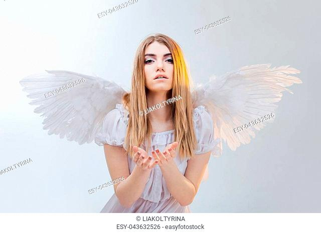 Young and wonderful blonde girl in the image of an angel with white wings