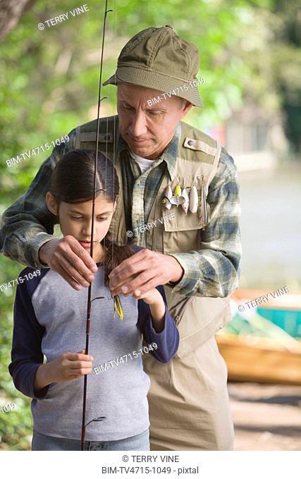 Hispanic grandfather helping granddaughter with fishing pole