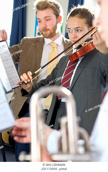 Music teacher teaching high school student playing violin in music class