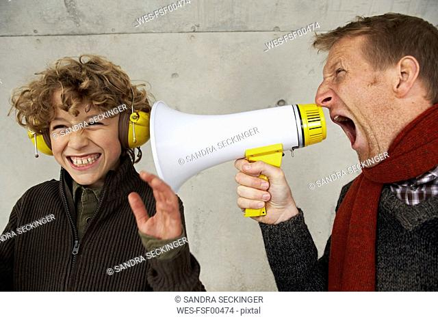 Father and son screaming at each other with magaphone