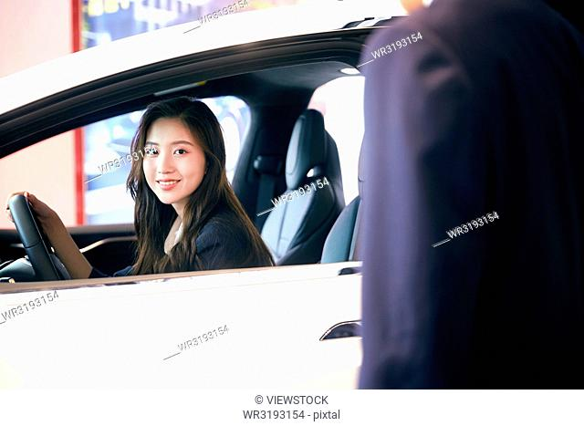 Young woman driving cars