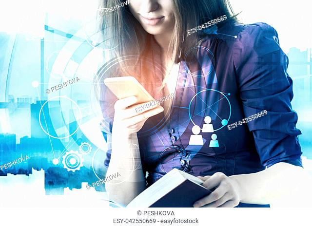 Businesswoman using smartphone with digital business interface and holding book on abstract city background. Online education, technology and future concept