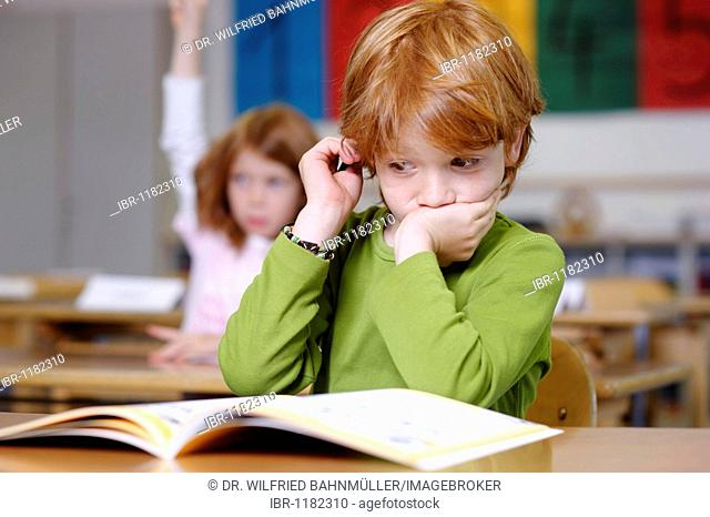 Children in primary school, boy daydreaming or looking unsure, thoughtful, sad or frustrated, boys becoming the losers or failures in the education system