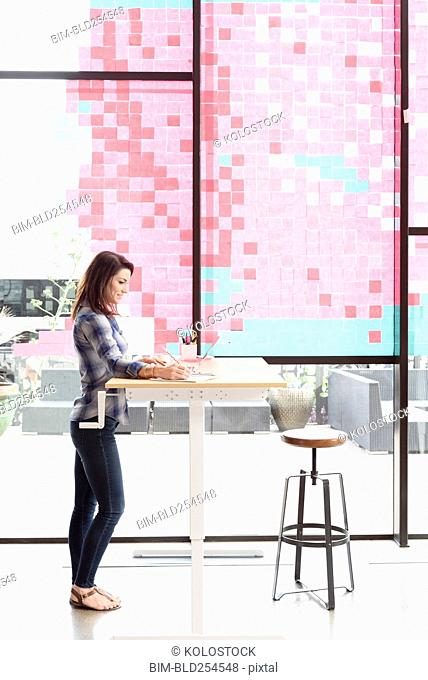 Caucasian woman using laptop at standing workstation